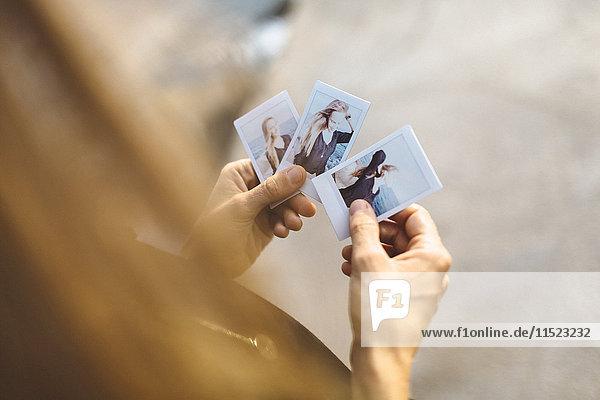 Junge Frau beim Betrachten von Sofortbildern von sich selbst Junge Frau beim Betrachten von Sofortbildern von sich selbst