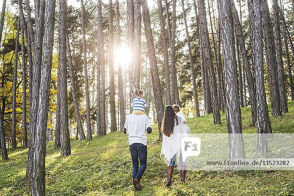 Familie mit zwei Mädchen  die im Wald spazieren gehen