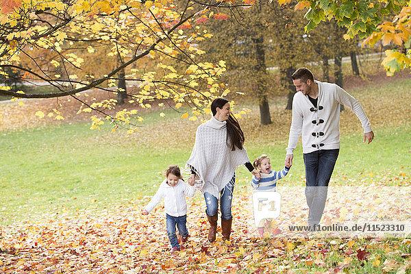 Glückliche Familie mit zwei Mädchen im Herbstlaub