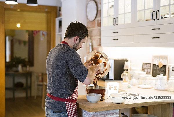 Mann steht in der Küche und backt Ringkuchen