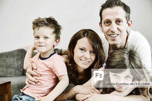 Glückliche Familie sitzt zu Hause auf der Couch