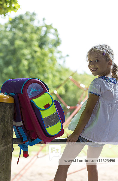 Smiling little girl with school bag sitting on high bar of a playground