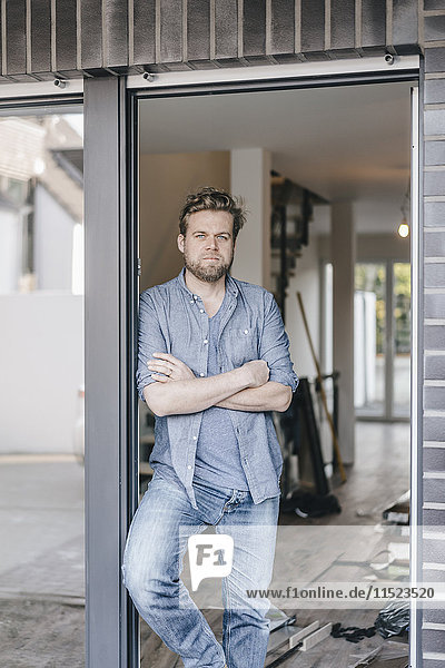 Der reife Mann steht in der Tür seines neuen Zuhauses.