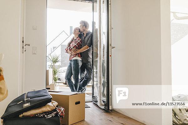 Ein glückliches Paar steht vor der Tür seines neuen Zuhauses.