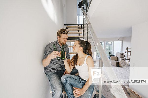 Paar im neuen Zuhause auf der Treppe sitzend  Toast mit Bierflaschen