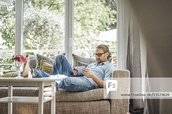 Mann entspannt auf der Couch mit Tablette