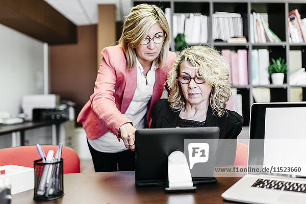 Zwei Geschäftsfrauen mit Laptop am Schreibtisch im Büro