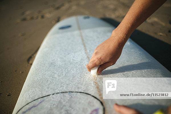 Frauenhand mit Paraffin auf dem Surfbrett  Nahaufnahme