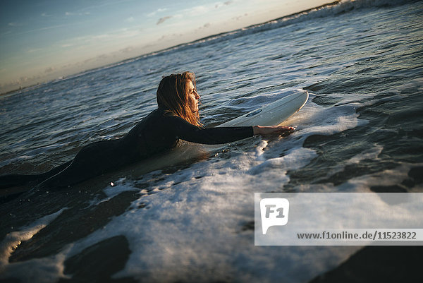 Frau auf dem Surfbrett im Meer liegend