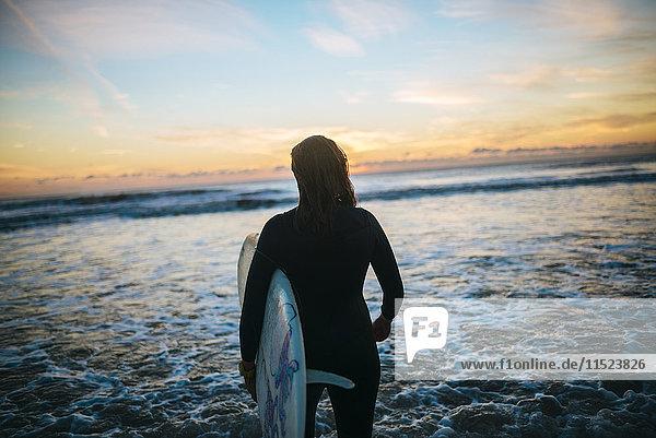Rückansicht einer jungen Frau mit Surfbrett  die am Strand steht und den Sonnenuntergang beobachtet.