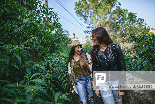 Two happy young women walking on a path with plants
