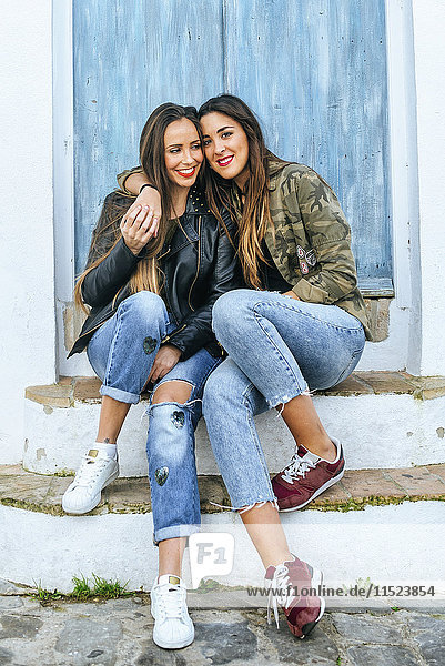 Two smiling young women sitting on stoop hugging