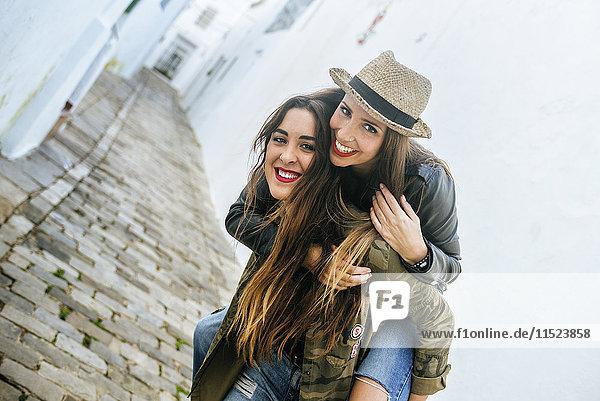 Fröhliche junge Frau beim Huckepack-Fahren mit einem Freund