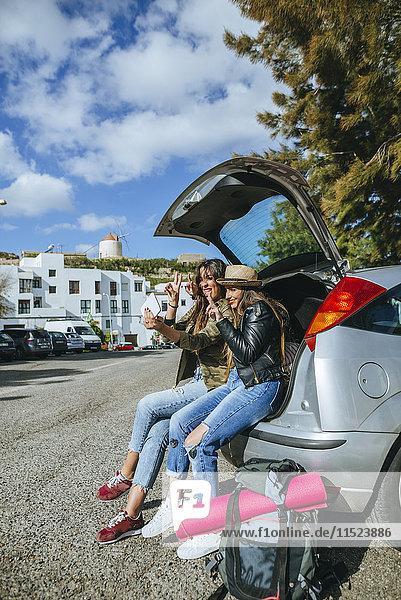 Junge Frauen nehmen einen Selfie  der im Kofferraum eines Autos sitzt.