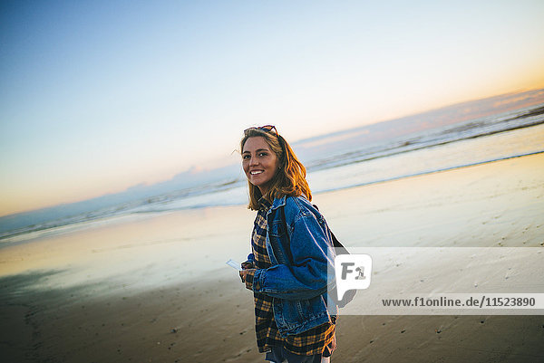 Portrait of smiling young woman on the beach at sunset