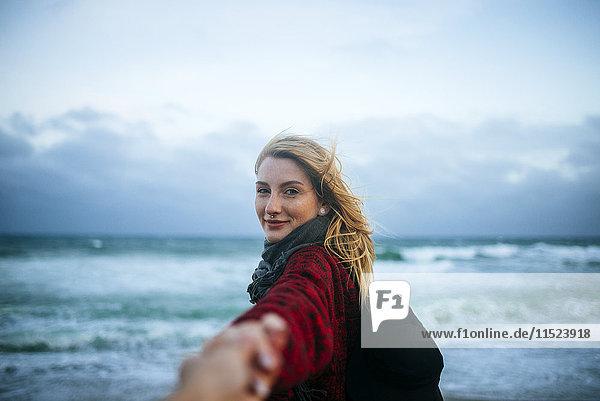 Junge Frau an der Hand eines Mannes am Strand Junge Frau an der Hand eines Mannes am Strand