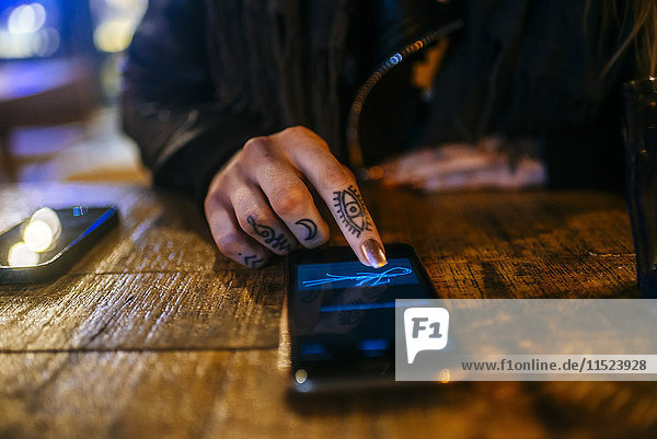 Nahaufnahme der Hände einer tätowierten Frau  die auf einem Smartphone unterschreibt.