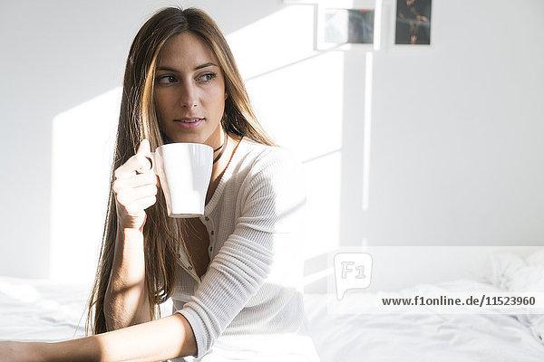 Junge Frau sitzt auf dem Bett und hält eine Tasse Kaffee.