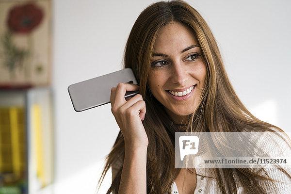 Lächelnde junge Frau hält Handy in der Hand