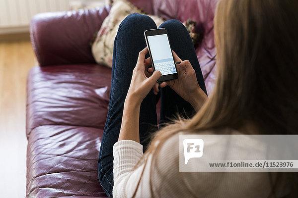 Junge Frau auf der Couch Textnachricht