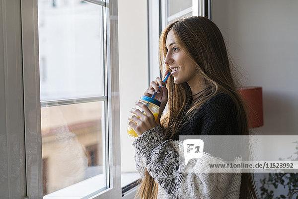 Junge Frau am Fenster trinkt hausgemachtes Getränk