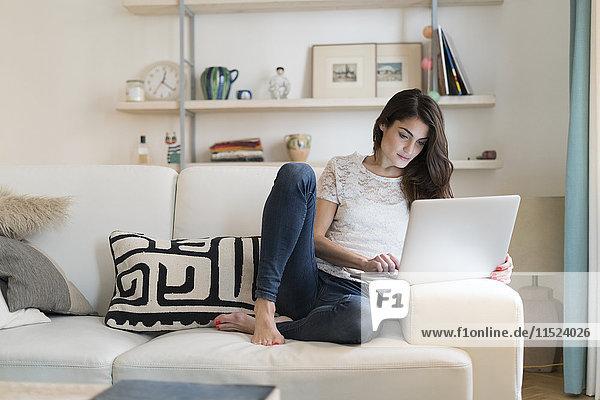 Frau sitzt auf der Couch zu Hause mit Laptop