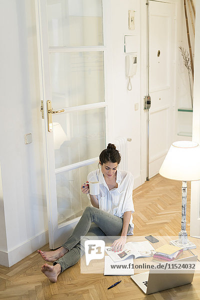 Junge Frau auf dem Boden sitzend mit Kaffeetasse  Katalog und Laptop
