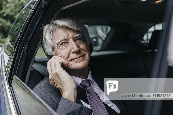 Porträt eines nachdenklichen Geschäftsmannes  der durch das Autofenster schaut.