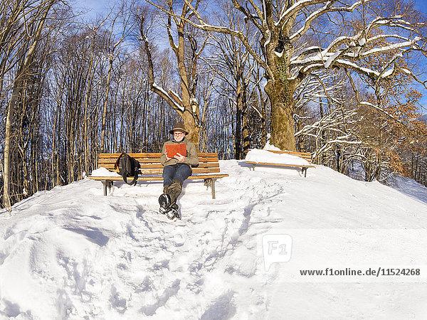 Deutschland  Kochel am See  Senior auf der Bank sitzend  E-Book lesen im Winter