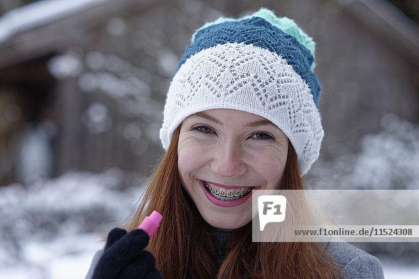 Portrait of happy teenage girl holding lip balm