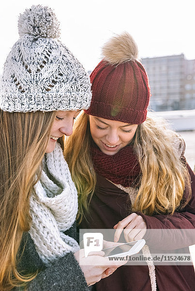 Two teenage girls wearing bobble hats and scarfs looking at smartphone