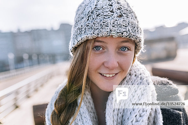 Portrait of smiling teenage girl wearing woolly hat and scarf