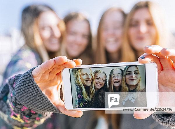 Gruppenbild von vier Freunden auf dem Display des Smartphones  Nahaufnahme