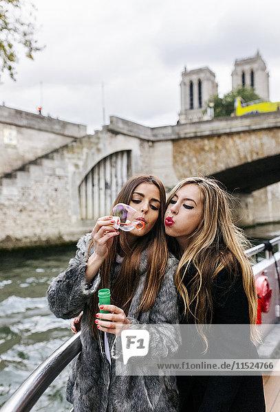 Paris  France  portrait of two friends blowing soap bubbles together