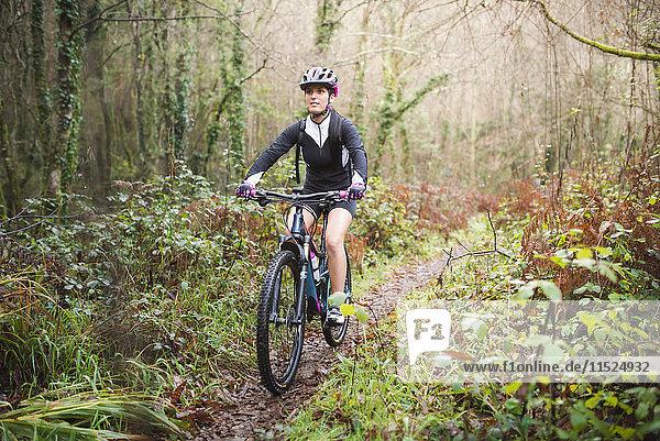 Mountainbike-Fahrerin auf einem Waldweg
