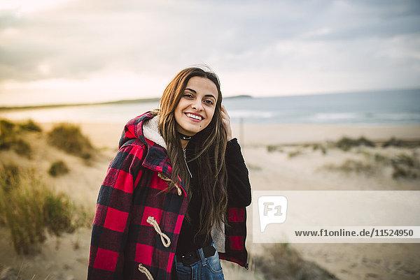 Porträt einer entspannten jungen Frau am Strand