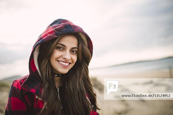 Porträt einer lächelnden jungen Frau in Kapuzenjacke am Strand