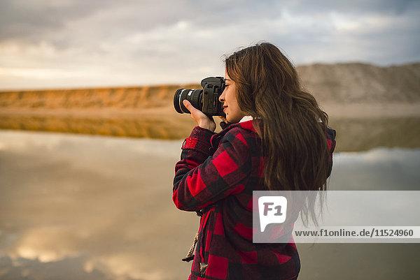 Junge Frau beim Fotografieren am Strand mit Kamera bei Sonnenuntergang