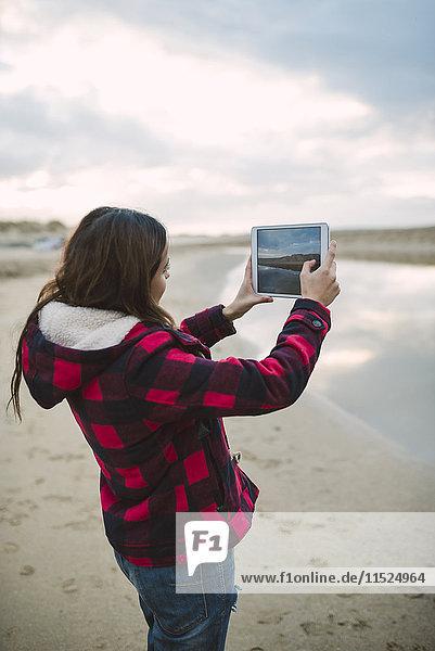 Junge Frau beim Fotografieren mit Tablette am Strand