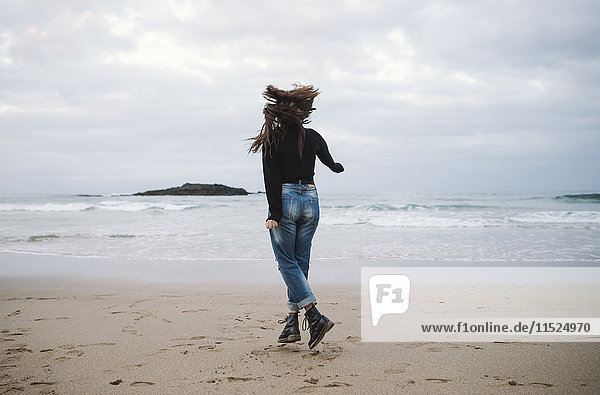 Back view of young woman jumping on the beach