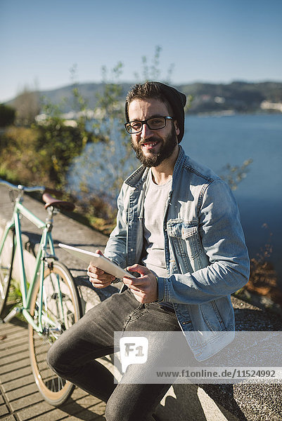 Lächelnder junger Mann mit einer Tafel am Wasser