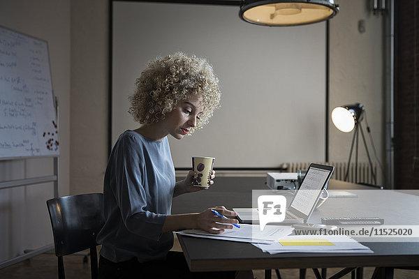 Frau arbeitet an Laptop und Dokumenten im Büro