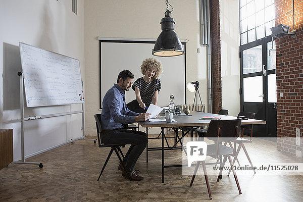 Mann und Frau diskutieren Dokument im Sitzungssaal