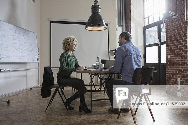 Mann und Frau diskutieren im Sitzungssaal