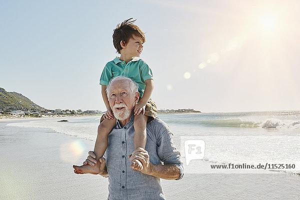 Porträt eines älteren Mannes mit Enkel auf den Schultern am Strand