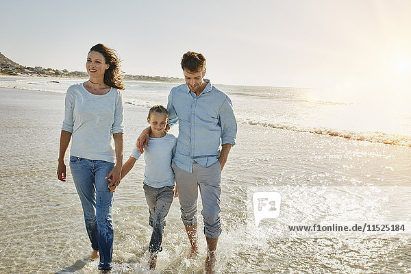 Couple with daughter walking on the beach