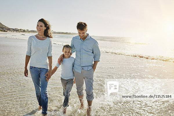 Paar mit Tochter  die am Strand spazieren geht