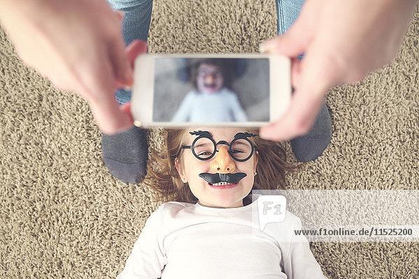Mutter fotografiert ihre Tochter mit dem Smartphone