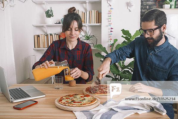 Junges Paar isst Pizza und trinkt Saft zum Mittagessen  Laptop steht auf dem Tisch