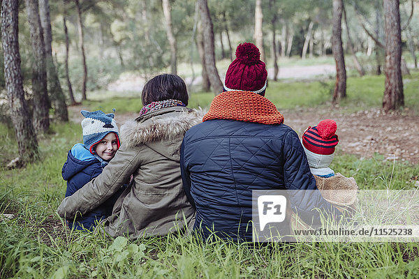 Rückansicht der im Wald sitzenden Familie